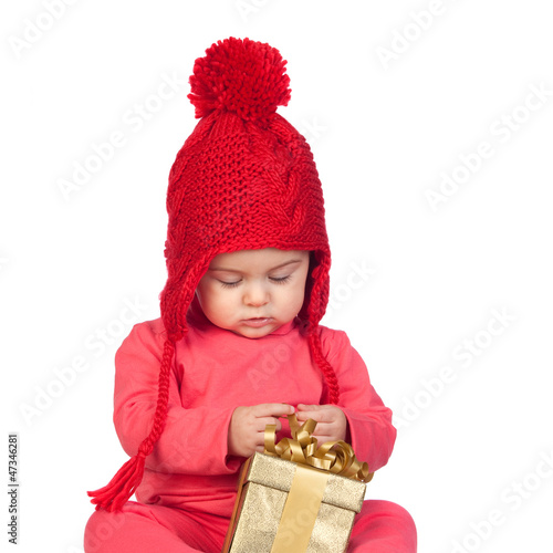 Baby girl with wool hat looking a gift