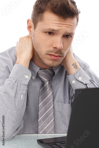 Tired businessman working on laptop