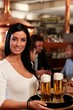 Beautiful waitress serving beer