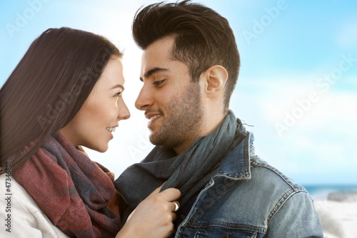 Loving couple kissing on the beach at autumn