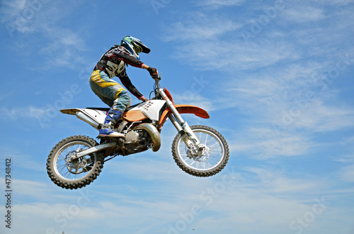 High flight by motorcycle racer motocross against the blue sky