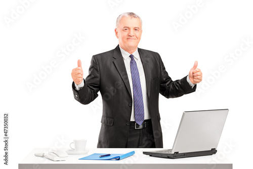 Happy mature businessman standing and giving thumbs up