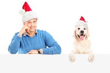 Smiling guy and dog wearing santa claus hats and posing behind a