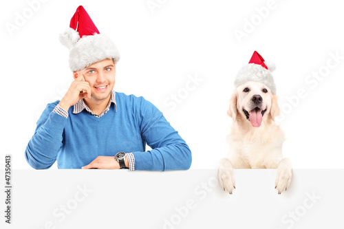 Smiling guy and dog wearing santa claus hats and posing behind a