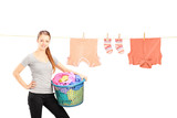 Smiling woman holding a laundry basket and a laundry line with c