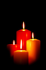 Four Christmas candles on black