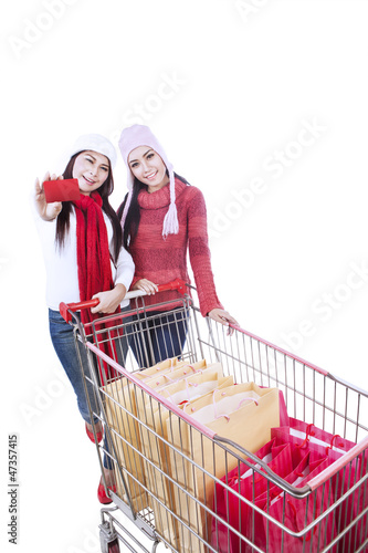 Happy winter shopping trolley with friend-isolated
