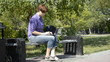 Girl uses a laptop on a park bench