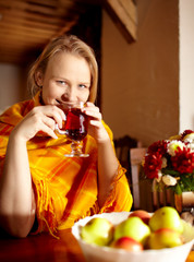 Young woman is drinking tea and smiling.