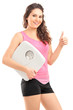 Happy female holding a weight scale and giving a thumb u