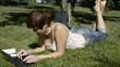 Young woman lying on grass with laptop