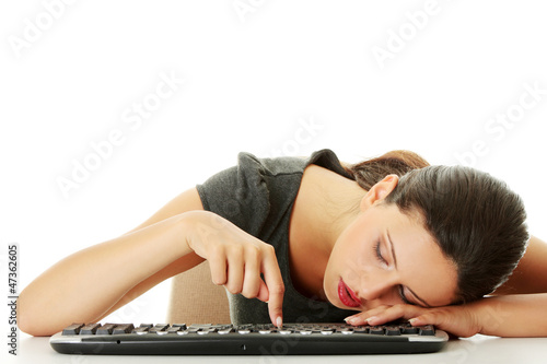 Tired businesswoman typing on keyboard