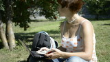 Young woman sitting on the grass in the park and chatting