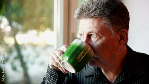 adult man standing near the window with a cup of tea 2
