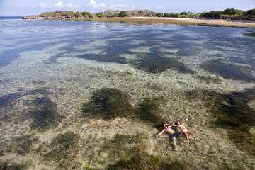 Couple lying on coast Bali, travel concept