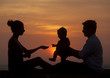 Silhouette of family sitting together at evening