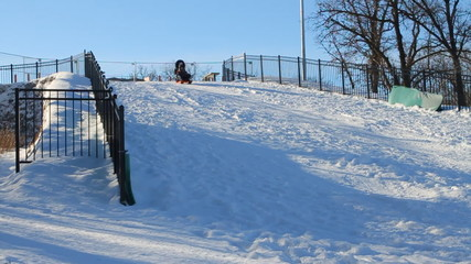 Woman and child fun sledding down hill in the snow