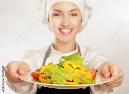 Pretty cook chief holding salad