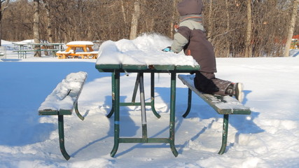 Boy removes snow from a table in the park in winter.