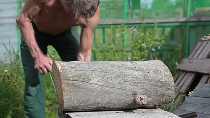 Man trying to start chainsaw for cutting the log