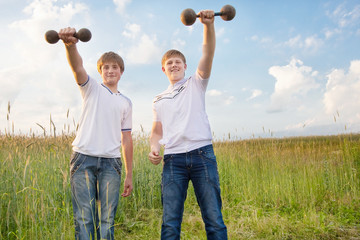 two teenagers with dumbbels