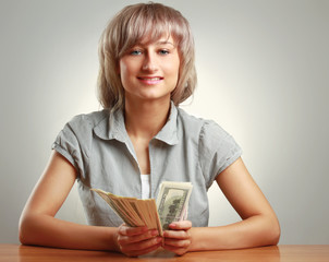 A young woman holding dollars