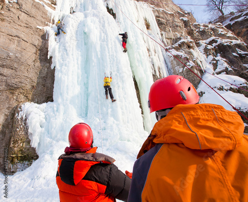Man supports climber on frozen waterfall