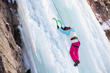 Woman climbing frozen waterfall
