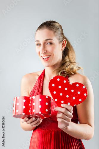 Frau öffnet Geschenk zum Valentinstag
