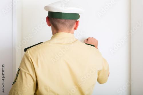 Leinwanddruck Bild Polizist klopft bei Einsatz an Haustür