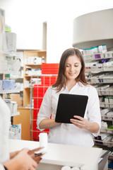 Pharmacist Helping Customer with Digital Tablet
