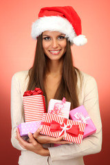 beautiful young woman with gifts, on red background