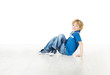 Smiling boy sitting down on floor over white background