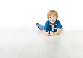 Smiling boy lying down on floor over white background