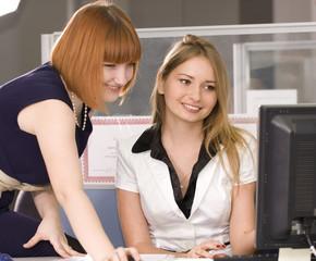 Smiling girl looking at a computer monitor