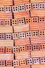 Orderly pile of construction red baked clay bricks