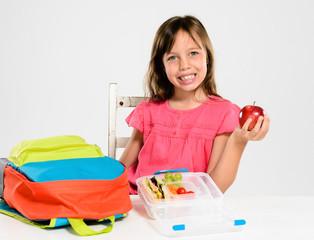 Elementary primary school girl holding red apple