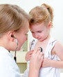 Female doctor examining little girl with stethoscope