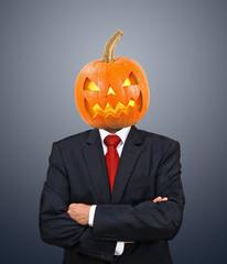 Geschäftsmann im Anzug mit Kürbiskopf zu Halloween