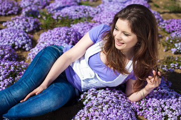 woman in park on background of bright violet flowers