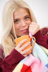 Woman sitting on the sofa, drinking tea