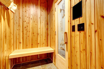 Home sauna with cedar wood walls and bench.