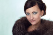 Portrait of cute woman with blue eyes in fur coat
