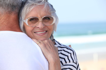 Elderly couple hugging on beach