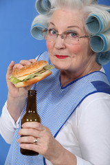 Old woman in rollers with a burger and a beer