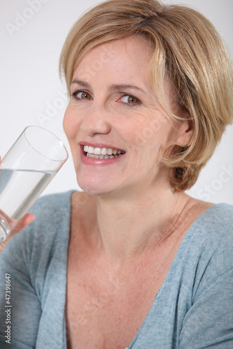 Closeup of healthy woman drinking a glass of pure water