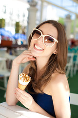 Beautiful young woman relaxing in bar with ice cream