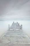 Fototapety Wooden pier on lake in a cloudy and foggy mood.
