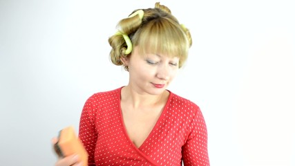 housewife in curlers with cleaner and sponge