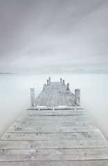 Wooden pier on lake in a cloudy and foggy mood. © stevanzz